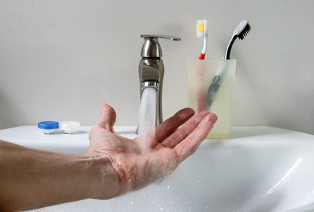 hygienic: Close-up of bathroom white sink, faucet, hygienic set and washing hand
