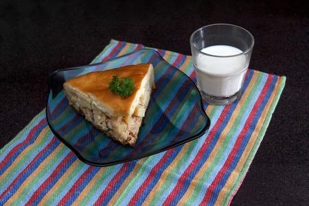 segmento: Primer plano de un segmento de pastel de pollo y papa con un vaso de leche contra el m�rmol negro fondo de la vista 2
