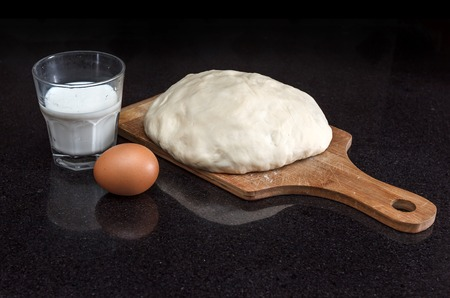Closeup of pastry dough on baking board and egg with milk on black marble table view 4 photo