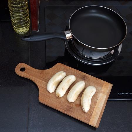 platanos fritos: Proceso de pl�tanos fritos Cocinar con huevos revueltos, corte los pl�tanos a bordo cerca de la sart�n, vista desde arriba Foto de archivo