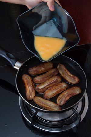 platanos fritos: Proceso de pl�tanos fritos Cocinar con huevos revueltos, manos vertiendo huevo revuelto en sart�n con pl�tanos fritos, ver 1 Foto de archivo