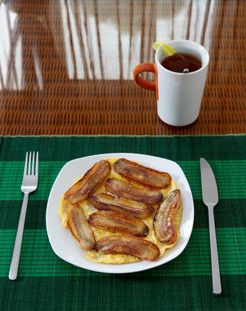 platanos fritos: Banano frito con huevos revueltos en un plato blanco sobre mantel de bambú verde y una taza de té con limón