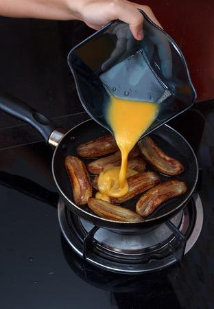 platanos fritos: Proceso de pl�tanos fritos Cocinar con huevos revueltos, manos vertiendo huevo revuelto en sart�n con pl�tanos fritos, ver 2