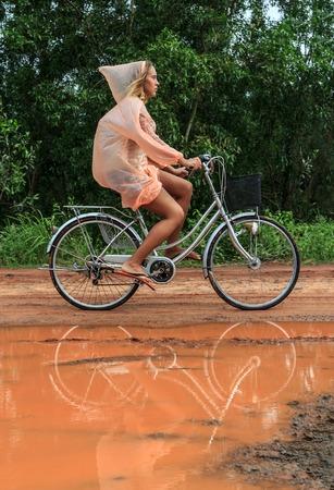 coutryside: Young woman riding bicycle in orange raincoat along orange puddle on coutryside ground road on a summer day
