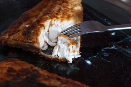 horozontal: A piece of fish fillett fried in batter served on blue glass plate with fork horozontal view 2 Stock Photo