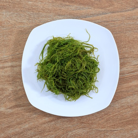 Fresh seaweed salad on white plate against wooden background, top view