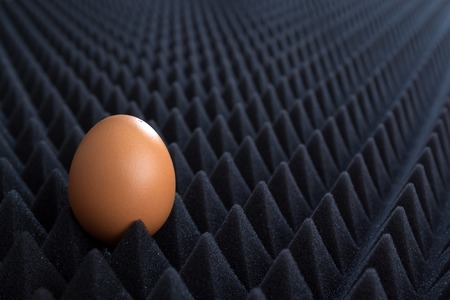 bumpy: one egg on abstract bumpy black background with perspective, horizontal view 1