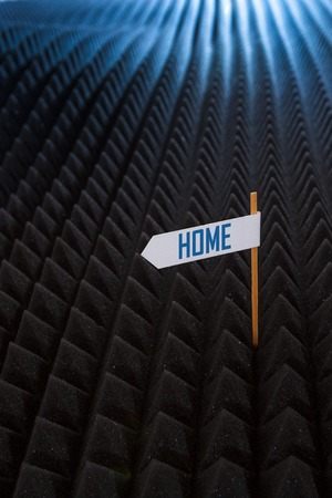 directional: white directional sign saying HOME on bumpy black background Stock Photo