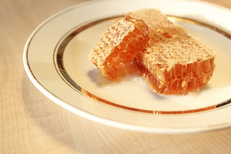 honey comb: Photo with seletive focus of stacks of honey comb on a plate on wooden table, horizontal view