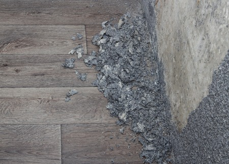 dismantle: Dismantle process of grey wall stucco with crushed pieces on floor Stock Photo