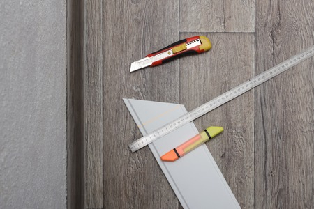 Home improvement. Measuring and cutting process of plastic panel on wooden floor. Top view 2 Stock Photo