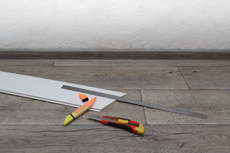 Home improvement. Measuring and cutting process of plastic panel on wooden floor. Horizontal view with copyspace