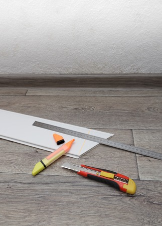 Home improvement. Measuring and cutting process of plastic panel on wooden floor. Vertical view with copyspace