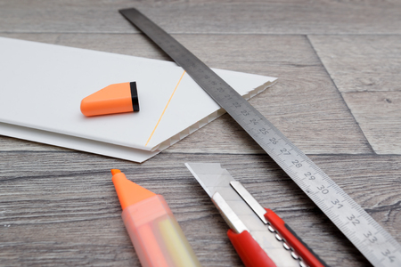 Home improvement. Measuring and cutting process of plastic panel on wooden floor. Shallow DOF photo Stock Photo