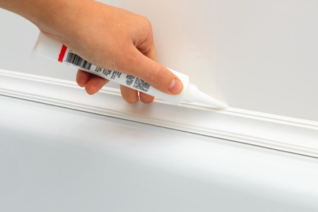 hermetic: Close up of hands caulking bath tube with white silicone glue horizontal view 2