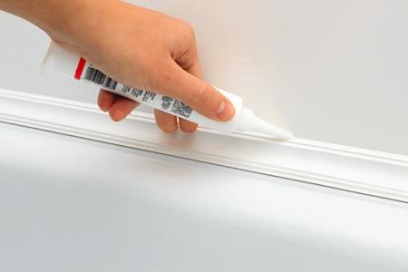 caulking: Close up of hands caulking bath tube with white silicone glue horizontal view 2