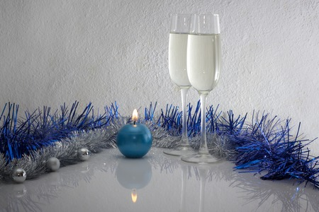 candlelit: Greeting card made of christmas and yew year decoration balls, tinsel, candel  and two glasses of champagne with reflection, copy space