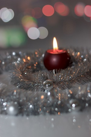 grey scale: Greeting card made of silver tinsel with silver christmas balls, red burning candle and bokeh lights at background, copy space Stock Photo