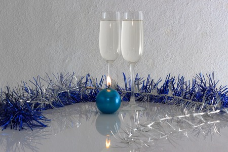 candlelit: Greeting card made of christmas and yew year decoration balls, tinsel, candel  and two glasses of champagne with reflection, copy space, horizontal view 2
