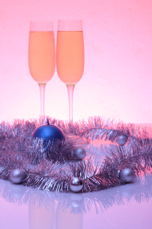 tinted glasses: Soft tinted photo of christmas and New Year decoration balls, tinsel, candel  and two glasses of champagne with reflection Stock Photo