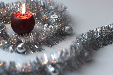 grey scale: Christmas greeting card made of silver tinsel with silver christmas balls and red burning candle, copy space