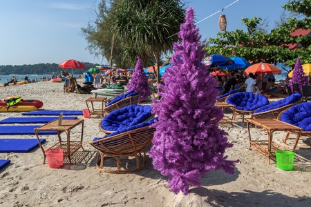 fake christmas tree: SIHANOUKVILLE, CAMBODIA - DECEMBER 31, 2014: Purple fake christmas tree on tropical beach with chairs and tables around in Sihanoukville, Cambodia on December 31, 2014