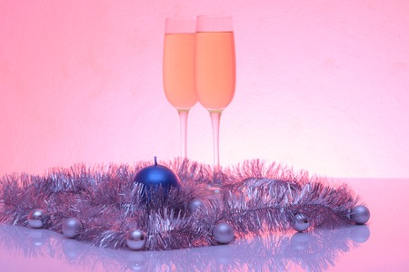 tinted glasses: Soft tinted photo of christmas and New Year decoration balls, tinsel, candel  and two glasses of champagne with reflection, horizontal view Stock Photo