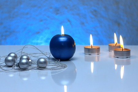 tea candles: Greeting card template made of blue and tea candles, silver christmas balls and silver string of beads  with copy space