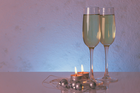tinted glasses: Special tinted photo of greeting card template made of two glasses of champagne with two candles, christmas balls and  string of beads with copy space, horizontal view