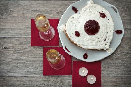 marmelade: Heart shaped cake with red marmelade, two glasses of champagne and two candles served on napkins against wooden background for romantic date, horizontal top view