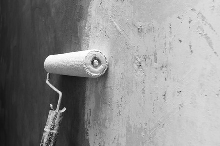 Paint roller applying paint on white wall, home improvements, horizontal view, grey scale photo with shallow DOF