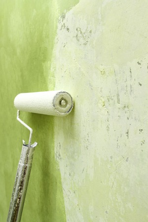 dof: Paint roller applying green paint on white wall, home improvements, shallow DOF