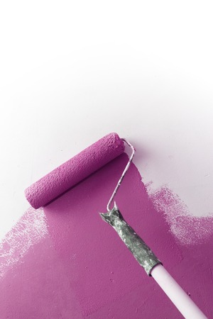 improvements: Paint roller applying purple paint on white wall, home improvements, copy space