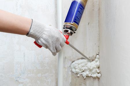 pulverizador: la mano del trabajador de fijar un alquiler en pared mediante espuma de poliuretano, vista horizontal