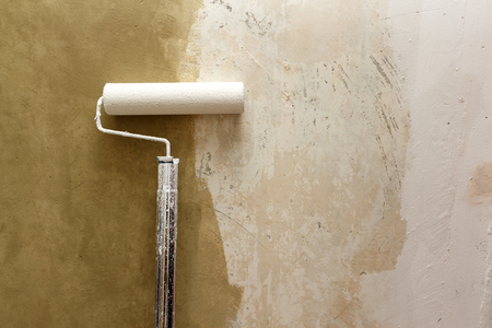 improvements: Paint roller applying brown paint on white wall, home improvements, horizontal view Stock Photo
