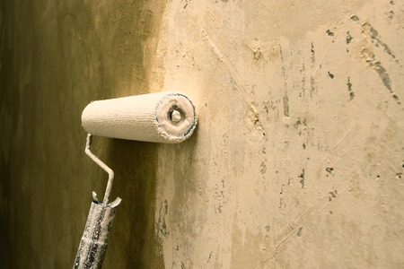 dof: Paint roller applying brown paint on white wall, home improvements, horizontal view shallow DOF