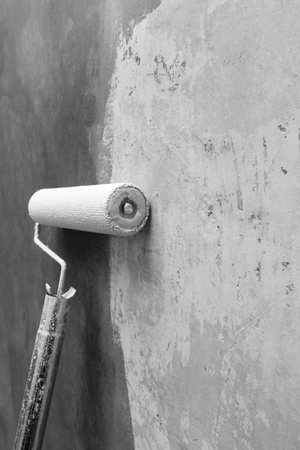 grey scale: Paint roller applying paint on white wall, home improvements, grey scale photo with shallow DOF Stock Photo