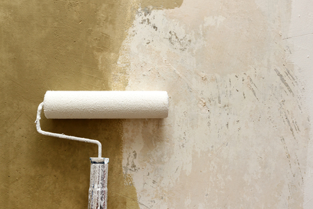 improvements: Closeup of paint roller applying brown paint on white wall, home improvements, horizontal view