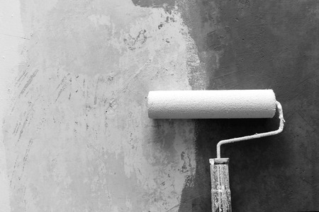 improvements: Closeup of paint roller applying paint on white wall, home improvements, grey scale photo, horizontal view Stock Photo