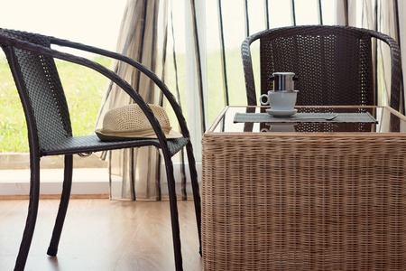 coffee filter: Morning coffee served in vietnam coffee filter on rattan table with two rattan chairs, natural light photo, horizontal view Stock Photo
