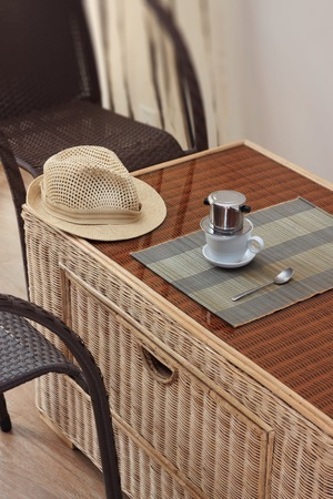 coffee filter: Morning coffee served in vietnam coffee filter on rattan table with two rattan chairs, natural light photo Stock Photo