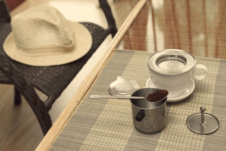coffee filter: Morning coffee served in vietnam coffee filter on rattan table with a hat on table, special tinted photo, closeup horizontal view