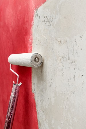 red paint roller: White paint roller and red paint on white wall ,home improvements