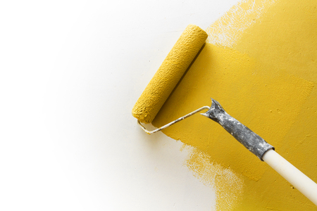 improvements: Paint roller applying yellow paint on white wall, home improvements horizontal view