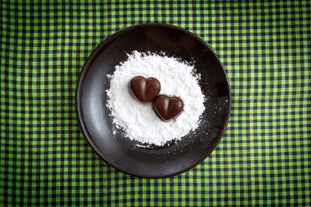 sugar powder: Two chocolate heart-shaped candies on a brown plate with sugar powder against green checked fabric background, horizontal top view