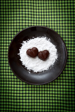 checked fabric: Two chocolate heart-shaped candies on a brown plate with sugar powder against green checked fabric background, top view Stock Photo