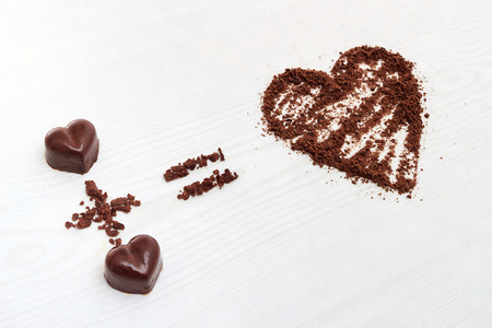horozontal: Love formula concept. Two chocolate candies make big love for chocolate. Horozontal view against wooden background Stock Photo