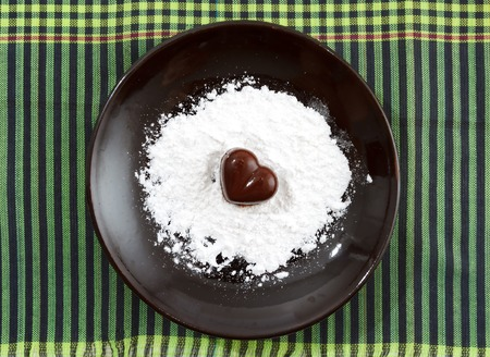 sugar powder: Chocolate heart-shaped candy on a brown plate with sugar powder against green checked fabric background, horizontal top view