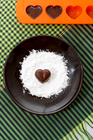 sugar powder: Chocolate heart-shaped candy on a brown plate with sugar powder and a bakin form with chocolates against green checked fabric background, top view Stock Photo