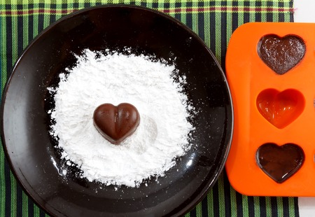 checked fabric: Chocolate heart-shaped candy on a brown plate with sugar powder and a bakin form with chocolates against green checked fabric background, horizontal top view